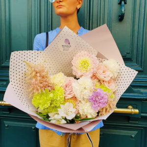 A stylish composition made with Dahlia, light pink Roses, Lisianthus and Astilbes wrapped in paper.