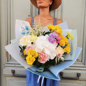 This bouquet is a mix of Hydrangea, yellow spray Roses, Lisianthus and Asstibles. Composition is wrapped in stylish paper.
